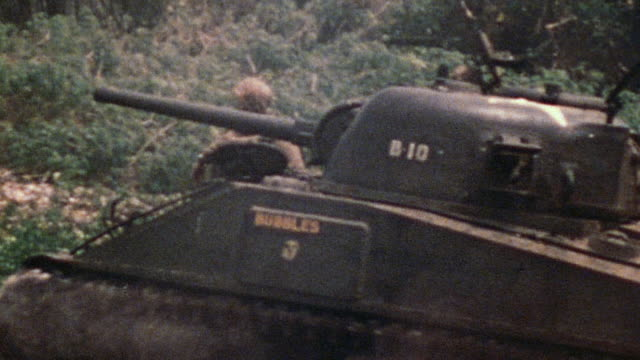 sherman tank with infantryman hitching a ride and self-propelled howitzer advancing behind / saipan, mariana islands - 1944 stock videos & royalty-free footage