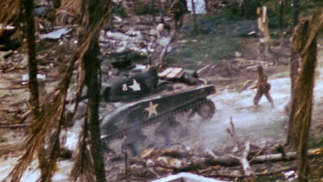 sherman tanks advancing followed by infantry and firing across chalky dirt road gunpowder smoke drifting / iwo jima japan - schlacht um iwojima stock-videos und b-roll-filmmaterial