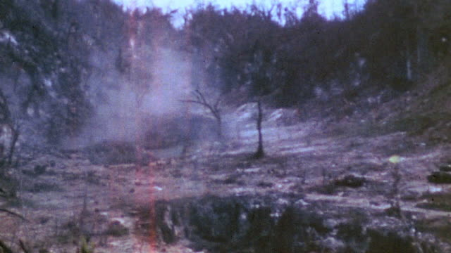 sherman tanks firing across blasted burned battlefield smoke drifting and peering over infantryman's shoulder at ridge / iwo jima japan - schlacht um iwojima stock-videos und b-roll-filmmaterial