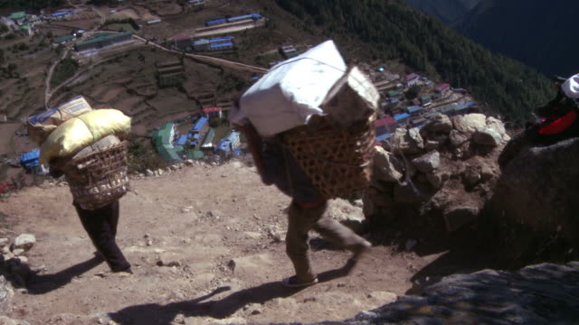 sherpa porters walking to namche bazaar, nepal carrying baskets. - carrying stock-videos und b-roll-filmmaterial