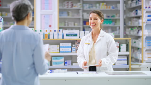 vídeos de stock e filmes b-roll de she's the friendliest pharmacist you'll find - farmácia