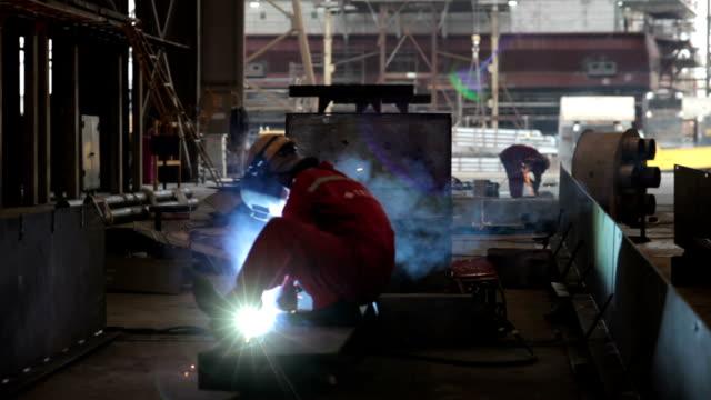 金属シールドアーク溶接機、シップヤード(ベトナム・サイゴンに - 造船所の労働者点の映像素材/bロール