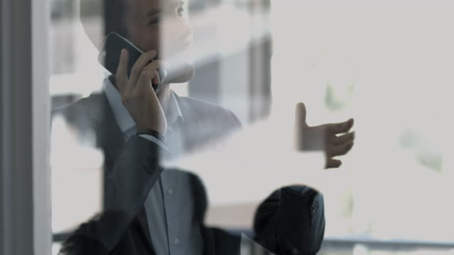 cu focus shift_businessman standing behind window with reflections, talking on phone - rack focus stock videos & royalty-free footage