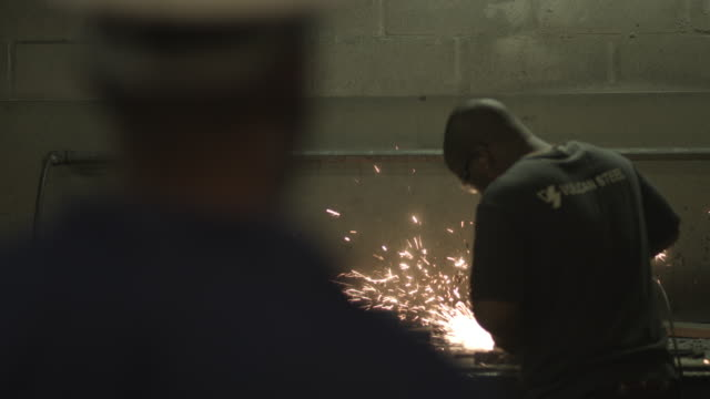 ms focus shift_overlooking shoulder of worker watching coworker polishing steel items - hand saw stock videos and b-roll footage