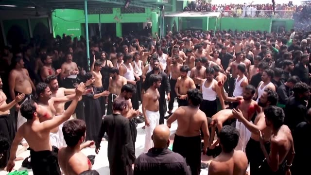 shiite muslim participate in a ritual of self flagellation during a religious procession held on the tenth day of the mourning period of muharram... - ashura muharram stock-videos und b-roll-filmmaterial