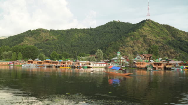 Shikara and houseboat on dal lake in summer
