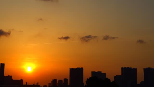 stockvideo's en b-roll-footage met shilouette bij zonsondergang urban skyline / contrail - low angle view