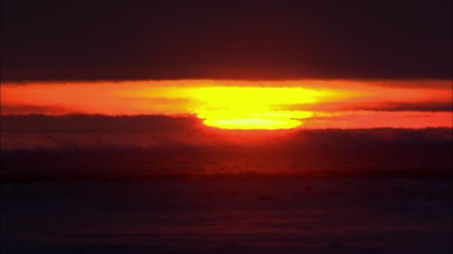 ws shimmering sun setting through hazy sky / churchill, manitoba, canada - seascape stock videos & royalty-free footage