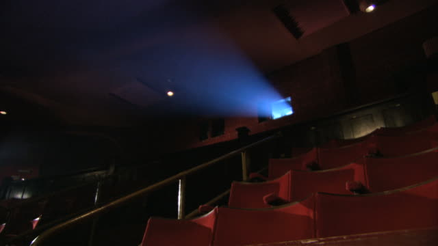 MS Shining light from projector room into dark empty theatre / London, Greater London, United Kingdom