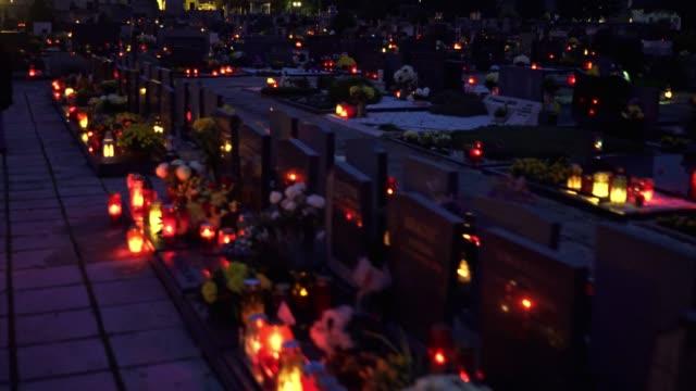 lichtgestalten in der abenddämmerung auf dem friedhof - friedhof stock-videos und b-roll-filmmaterial