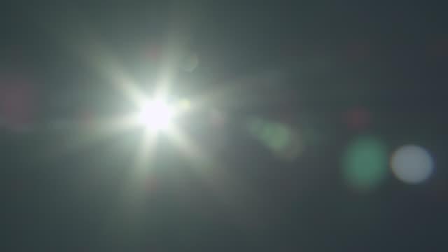 vídeos de stock e filmes b-roll de shining sun flares across dark sky, zambia - reluzente