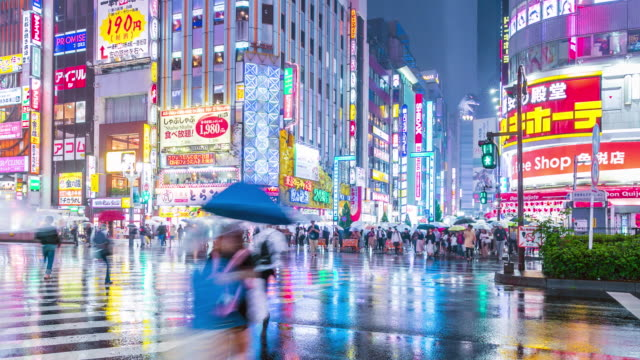shinjuku crowd crossing in the city at twilight while raining time lapse - conditions stock videos and b-roll footage