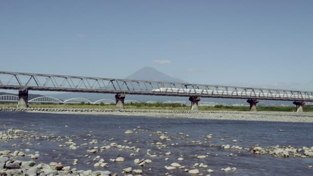 shinkansen crossing bridge in front of mt. fuji - satoyama scenery stock videos & royalty-free footage