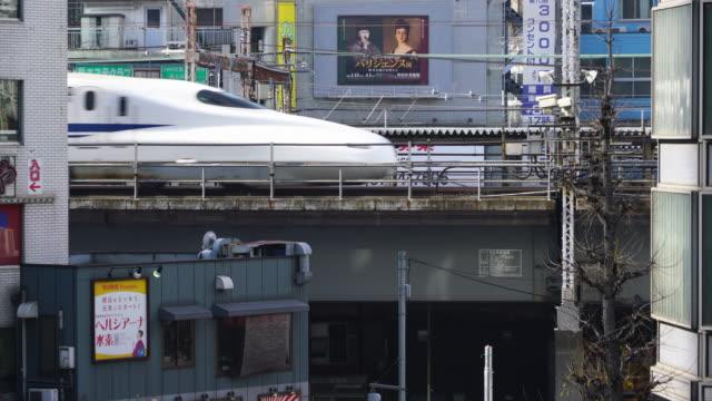 jr (japan railways) shinkansen runs on the elevated railway over the road among the row of izakaya (jappanese style bar restaurant) around shinbashi district at minato ward tokyo japan on jan. 18 2018. - elevated train stock videos & royalty-free footage