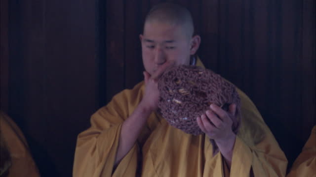 A Shinto monk plays a conch shell trumpet. Available in HD.