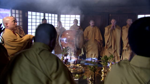 Shinto monks in yellow robes surround burning incense. Available in HD.