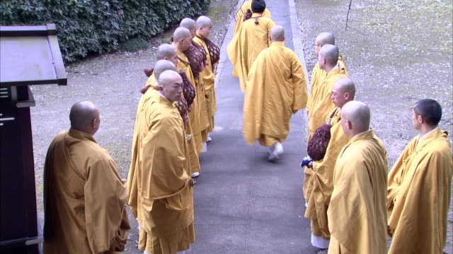 shinto monks in yellow robes walk through an archway in single file. available in hd. - shinto stock videos & royalty-free footage
