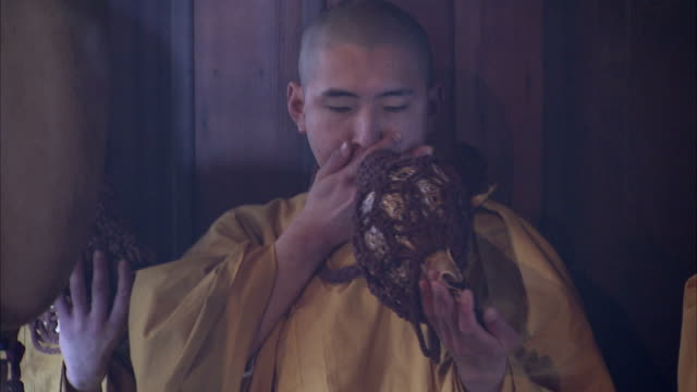 Shinto monks play conch shell trumpets during a ceremony. Available in HD.