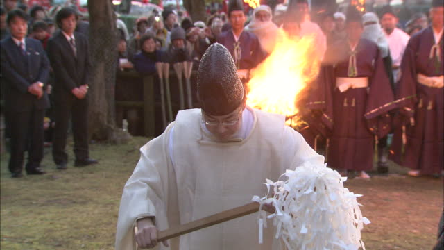 a shinto priest waves an onusa wand near a flaming brazier. - religious celebration stock videos & royalty-free footage