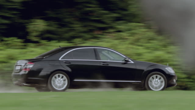 SELECTIVE FOCUS Shiny, black, luxury car speeding and kicking up dust before pulling up in front of a large residence with wooden doors
