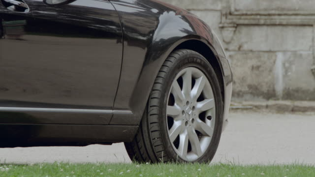 ts shiny, black, mercedes benz taking off and coming to a stop in front of a residence with large wooden doors - mercedes benz stock videos and b-roll footage