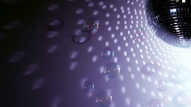 Shiny disco ball revolving with floating bubbles close up