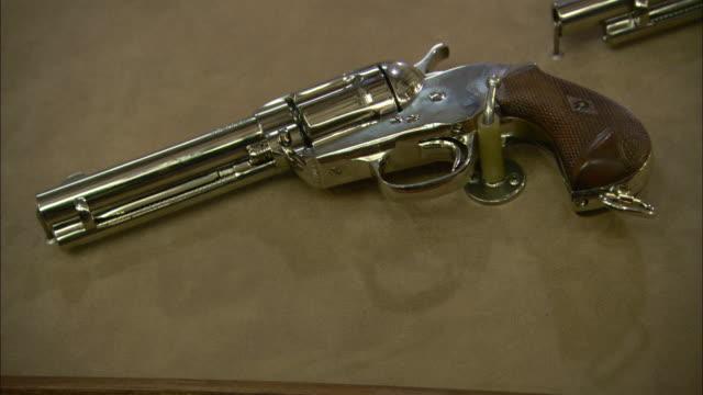 a shiny handgun gleams on a display. - handgun stock videos & royalty-free footage