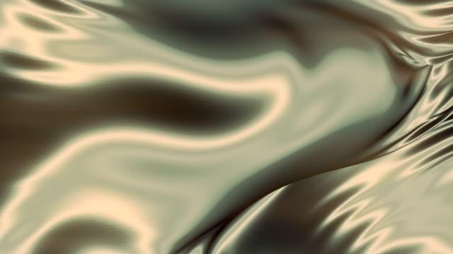 vídeos de stock, filmes e b-roll de pano metálico brilhante voando. pano de luxo de fundo dourado abstrato ou dobras onduladas design de fundo luxuoso. renderização 3d. 4k, resolução ultra hd - contorcido