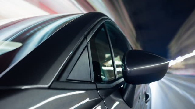 vídeos de stock, filmes e b-roll de shiny, reflective grey car drives fast through the city of berlin. - long exposure