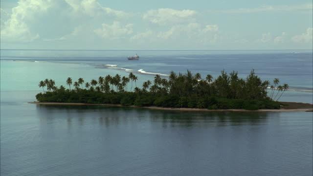 vidéos et rushes de aerial ws ls ship approaching tropical island - angle de prise de vue