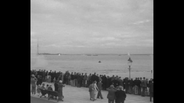 ship at sea surrounded by sailing yachts / shot of crowd on beach, cannon fires to start race, pan across crowd on beach to yachts in near distance... - regatta stock-videos und b-roll-filmmaterial