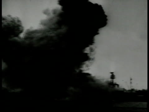 Ship being hit by bomb explosion black smoke TU WS Silhouette of twinengine airplanes in flight formation of threes WS Ship on fire WS Shoreline w/...