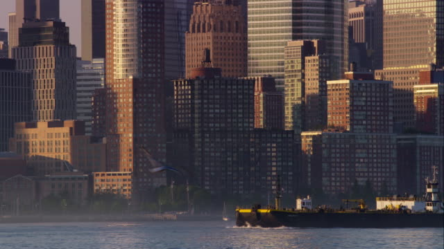 Ship crosses in front of New York City skyline.