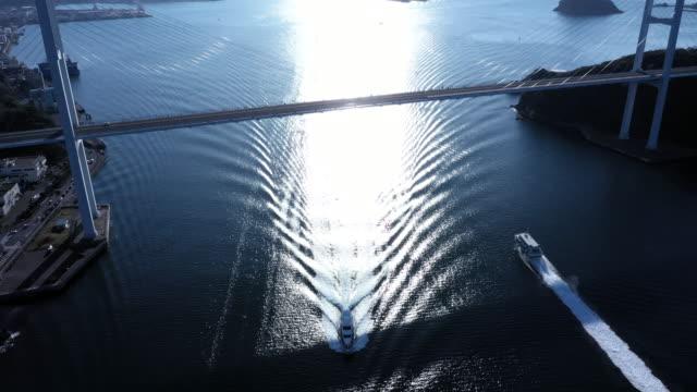 a ship crossing under the suspension bridge - フェリー船点の映像素材/bロール