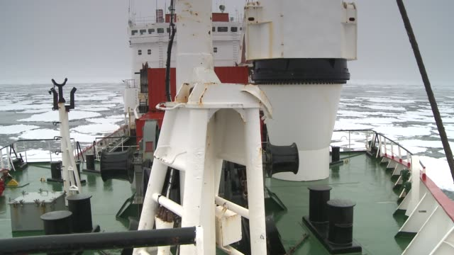 A ship cruises through sheets of ice in the Southern Ocean. Available in HD.