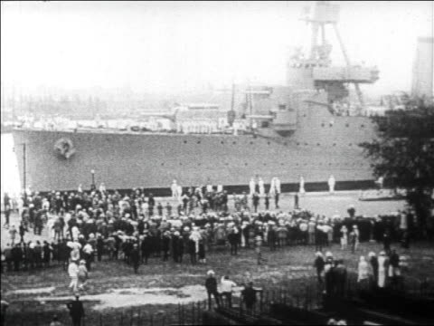 b/w 1927 ship docking as crowd rushes towards it / newsreel - warship stock videos & royalty-free footage