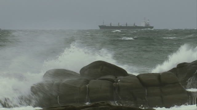 A ship drifts on the horizon as waves crash against the rocks of a beach, Available in HD.