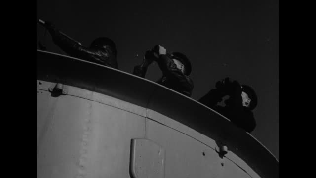 ship following wake of another in uk military convoy to britain; canadian sailors in dark coveralls seated on deck; man lights cigarette / vs side of... - sailor stock videos & royalty-free footage