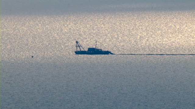 A ship glides across the glittering waters of the Gulf of Mexico.