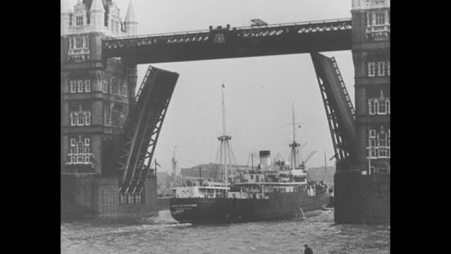 ship glides on the thames river under the tower bridge / note: exact month/day not known - newsreel stock videos & royalty-free footage