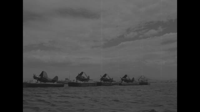 a ship hauls several barges and curtiss sb2c helldiver airplanes with their wings folded / personnel gathered around the airplanes / aboard aircraft... - folded stock videos and b-roll footage