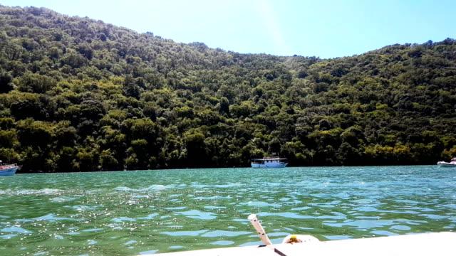 ターコイズ ブルーの海で出荷します。背景の木と青緑色の湾の生い茂った丘があります。 - hill点の映像素材/bロール