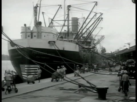 vidéos et rushes de ship in dock workers unloading. ms crate on crane 'ford made in canada.' worker carrying crate on shoulders walking over plank. box 'produce of... - 1942