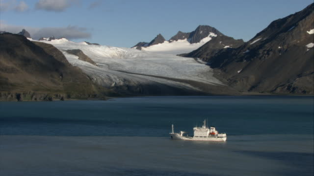 ws, ha, ship in sea, snow capped mountains in background, south georgia island - south georgia island stock videos & royalty-free footage