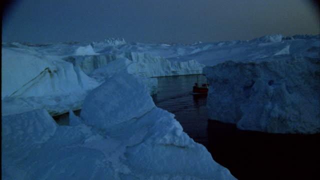 vídeos de stock e filmes b-roll de aerial a ship in the ocean approaching icebergs - clima polar
