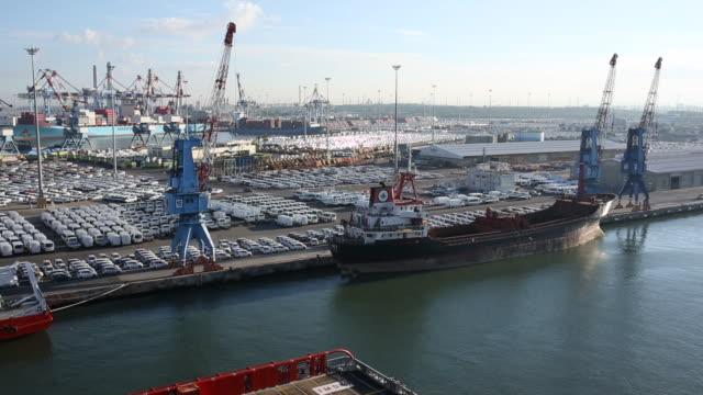 vídeos de stock e filmes b-roll de ship moves into busy port in early morning - ancorado