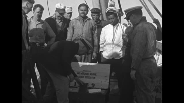 ship nantucket at sea / supplies being transferred from the anemone to the nantucket by rowboat / crew of nantucket watch as captain opens crates of... - 灯台船点の映像素材/bロール