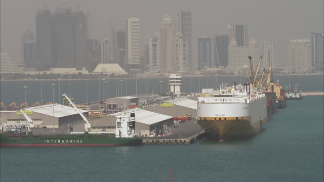 ws zo zi  ship on large dock seemingly floating in harbor of city with skyline of city / doha, qatar   - harbour stock videos & royalty-free footage