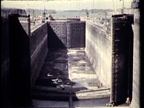 1958 WS PAN HA TU MS Ship passing through Panama Canal locks, locks filling with water, man walking along canal / Panama / AUDIO