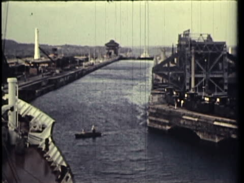 1958 WS PAN HA MS Ship passing through Panama Canal, workers working at canal construction, sailors walking on street, ship entering into lock / Panama / AUDIO